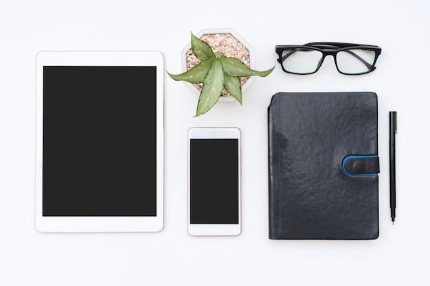 Scrivania da ufficio bianca con notebook, tablet, smartphone, occhiali e penna. telefono cellulare vuoto e blocco note per il testo di input. affari, concetto di finanza