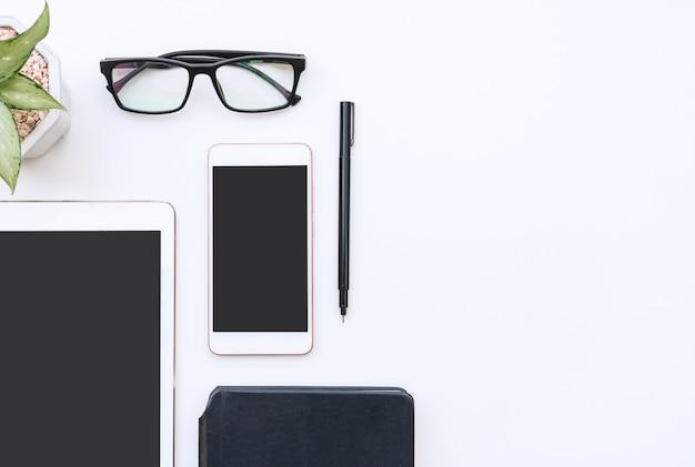 Scrivania da ufficio bianca con occhiali smartphone tablet notebook e spazio copia penna