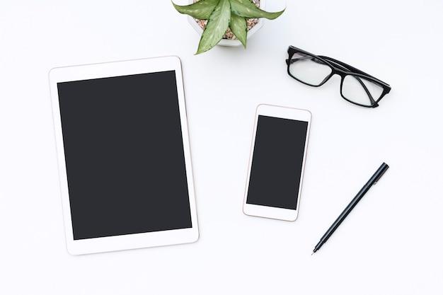 Scrivania da ufficio bianca con tablet, smartphone, occhiali e penna.