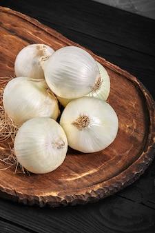 Cipolle bianche su una tavola di legno su sfondo nero. cibo organico