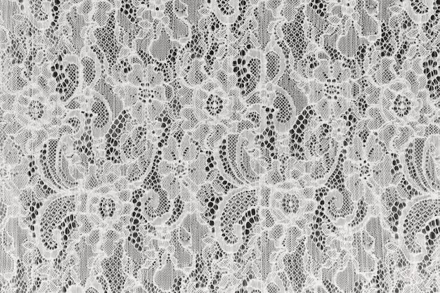 Trama di sfondo bianco pizzo traforato. tessuto guipure bianco con ornamento. pizzo delicato con motivo floreale