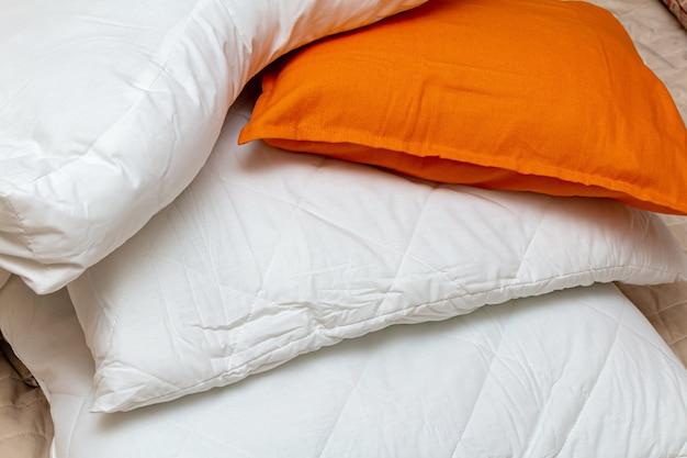 Mucchio bianco e arancione delle lenzuola coperte di cuscini con cuscini