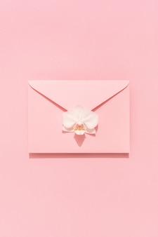 Fiore dell'orchidea bianca sulla busta rosa. biglietto di congratulazioni, donna, festa della mamma, san valentino, compleanno. sfondo vacanza.
