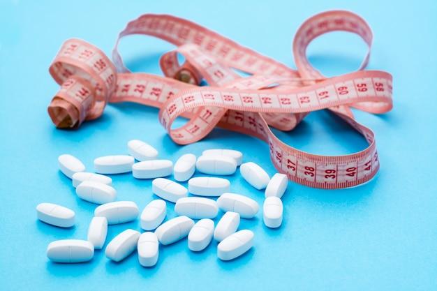 Pillole ovali bianche in nastro di misurazione sul blu.