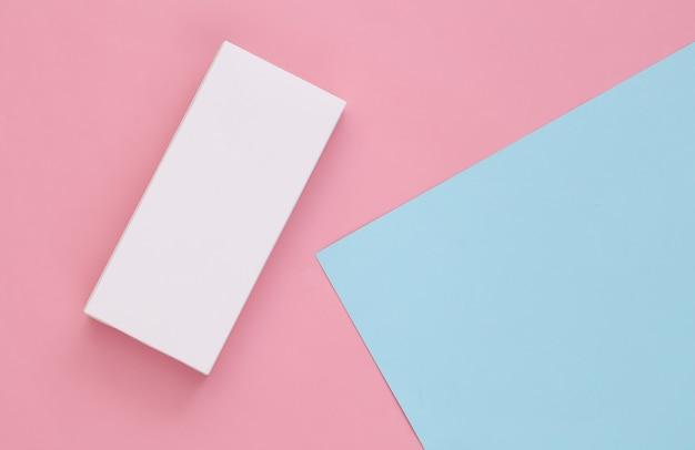 Scatola di imballaggio bianca su pastello rosa-blu. minimalismo. copia spazio