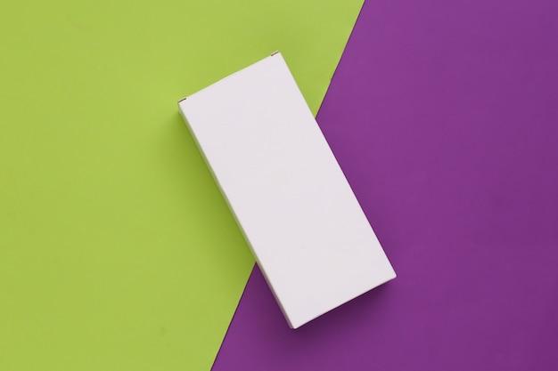Scatola di imballaggio bianca su verde viola. minimalismo