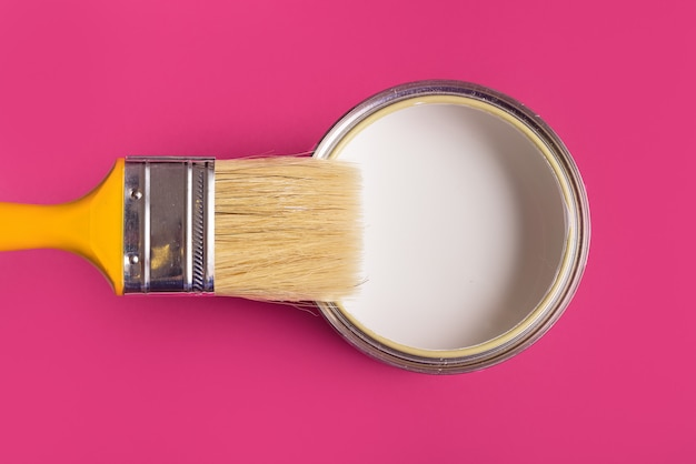 La vernice bianca può con la spazzola vista dall'alto su sfondo rosa.