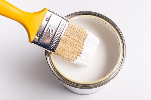La vernice bianca può con vista dall'alto pennello su sfondo bianco.