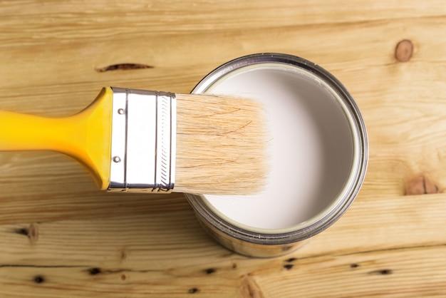 La vernice bianca può con la spazzola vista dall'alto su fondo di legno