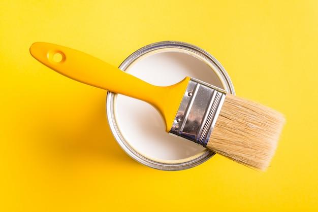 La vernice bianca può con vista dall'alto pennello su sfondo giallo