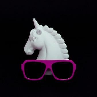 Unicorno dipinto di bianco e occhiali da sole eleganti nello spazio nero. arte dal design minimale