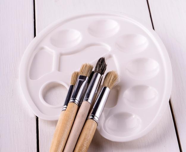 Tavolozza bianca e nuovi pennelli sul tavolo di legno bianco