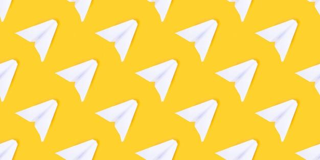 Aeroplano di carta bianco su sfondo giallo. concetto