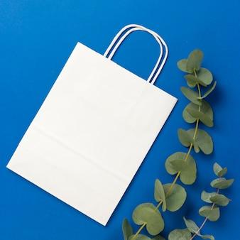 Sacchetto di carta bianco con manici e foglie di eucalipto sulla parete blu.