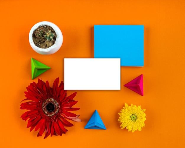 Carta bianca nota fiori luminosi composizione geometrica mockup biglietto di auguri copia spazio orange