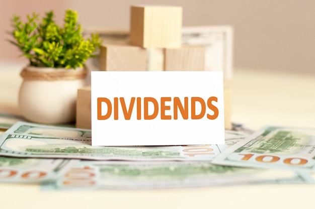 La carta di carta bianca con il testo dividendi è sulla superficie di soldi di carta, cubi di legno e fiori