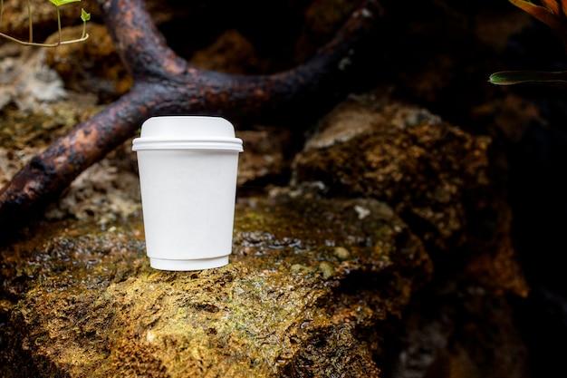 Tazza di caffè di carta bianca nella splendida natura