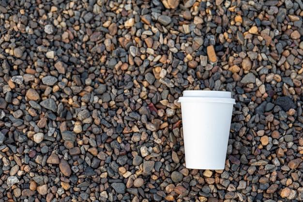 Una tazza di caffè o tè di carta bianca si trova sulla costa rocciosa. una tazza di bevanda calda su un ciottolo. bellissimo sfondo roccioso. spazio di copia gratuito.