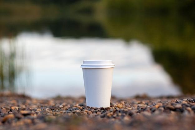Una tazza di caffè o tè di carta bianca si trova sulla riva rocciosa del lago. una tazza di bevanda calda su un ciottolo. bellissimo sfondo della natura del lago nella foresta dietro. spazio di copia gratuito.