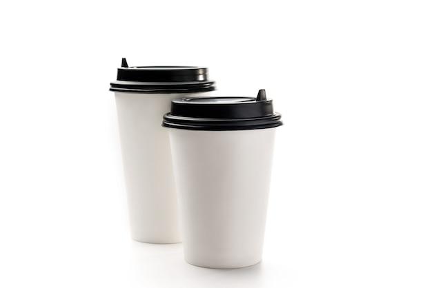 Bicchieri di carta bianca per bevande da asporto su uno sfondo bianco con spazio di copia. due tazze di caffè bianco.
