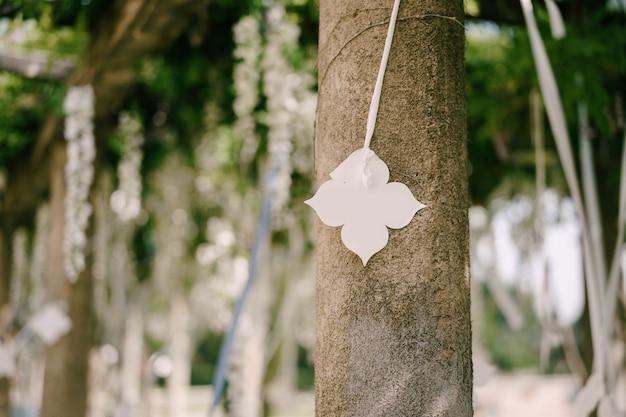 Fiore decorativo di carta bianca che appende su un nastro