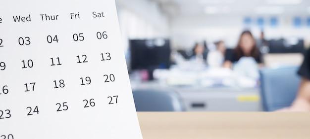 Calendario da tavolo in carta bianca sul piano del tavolo in legno con sfondo interno ufficio offuscato appuntamento e concetto di riunione d'affari