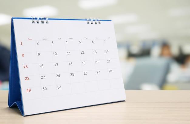 Calendario da tavolo di carta bianca sul piano del tavolo in legno con appuntamento sfocato sullo sfondo interno dell'ufficio e concetto di riunione d'affari