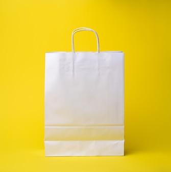 Sacchetto usa e getta in carta bianca con manici su fondo giallo, zero rifiuti