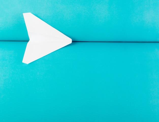 Origami dell'aereo di carta bianco su sfondo blu