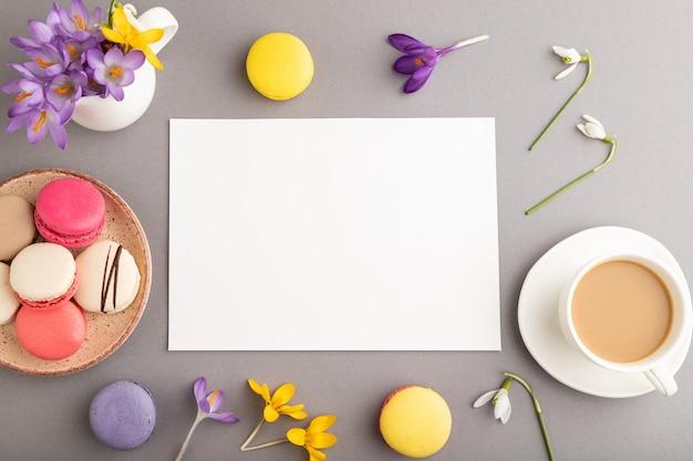 Mockup di fogli di carta bianca con fiori di croco bucaneve e amaretti su sfondo grigio pastello.