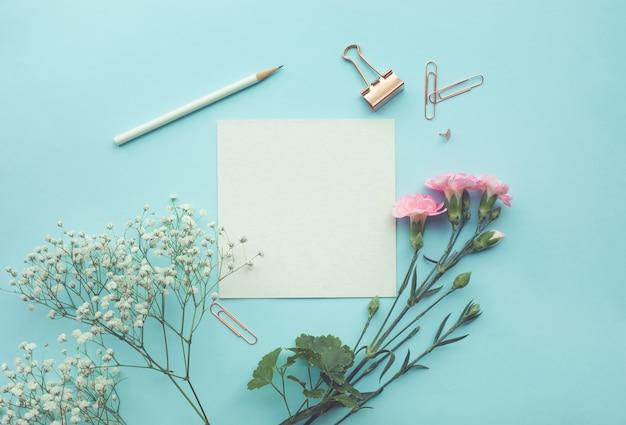 Spazio carta bianca con fiore su sfondo di colore pastello.