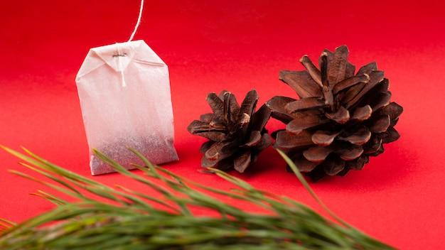 Bustina di tè di carta bianca con pigne e rami di abete rosso su un primo piano sfondo rosso, tè con aroma di foresta.