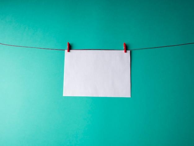 Libro bianco che pesa su una corda rossa ed è fissato con due mollette su uno sfondo verde. un modello per il tuo progetto per san valentino