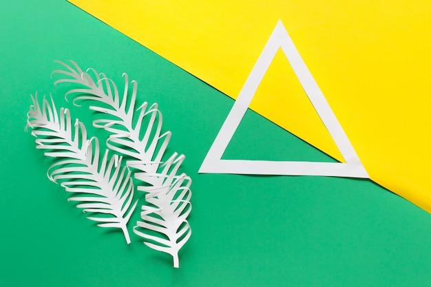 Triangolo di carta bianco e due piume di carta su giallo verde