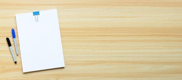 Libro bianco con clip legante e penne su sfondo texture in legno.