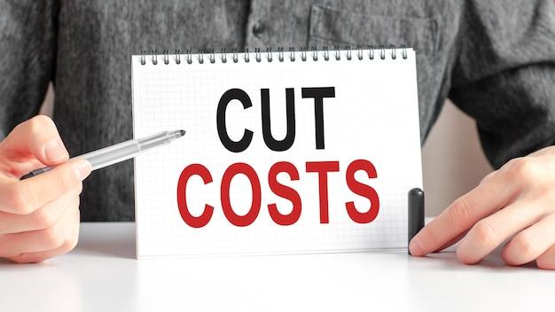 Carta bianca con la scritta tagliare i costi. concetto di affari.