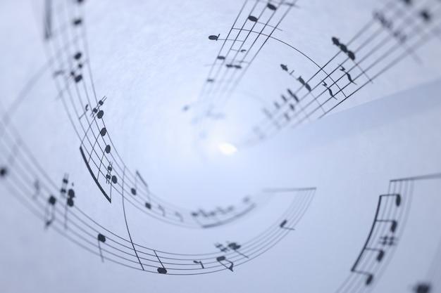 Libro bianco con note musicali arrotolate concetto di scrittura di musica di sottofondo del primo piano