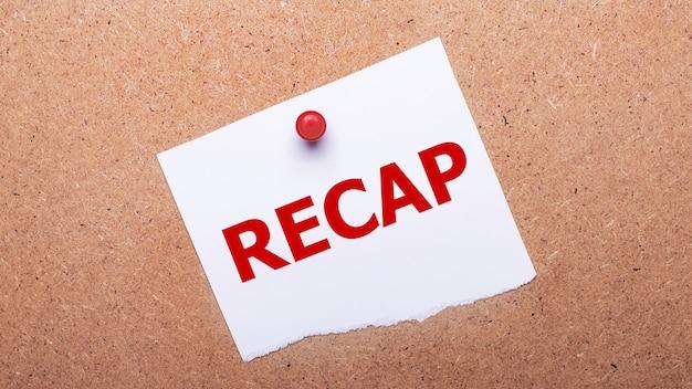La carta bianca con il testo recap è attaccata allo sfondo in legno con un pulsante rosso.