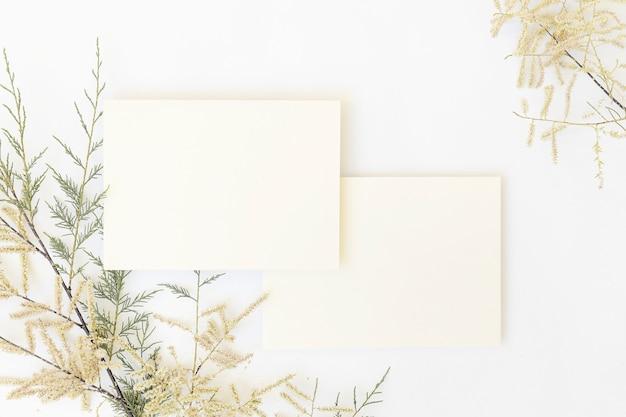 White paper e buste con foglia di palma tropicale