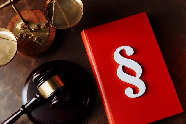 Simbolo di paragrafo bianco su un libro rosso e su un martelletto del giudice