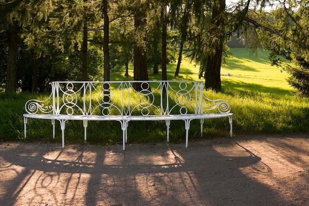 Panca modellata bianca in un parco estivo