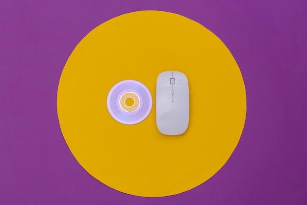 Mouse pc bianco e cd su sfondo viola con cerchio giallo. colpo concettuale dello studio. minimalismo. vista dall'alto
