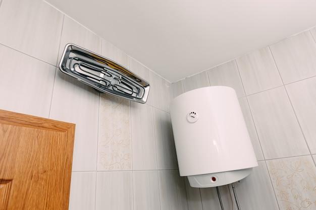 Caldaia a sospensione bianca con riscaldatore a infrarossi rettangolare con filamento su parete piastrellata bianca