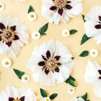 Modello di fiori di camomilla e peonie bianche su giallo