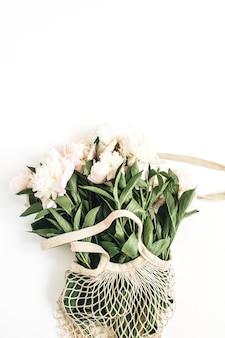 Fiori di peonia bianca in sacchetto di stringa sulla superficie bianca