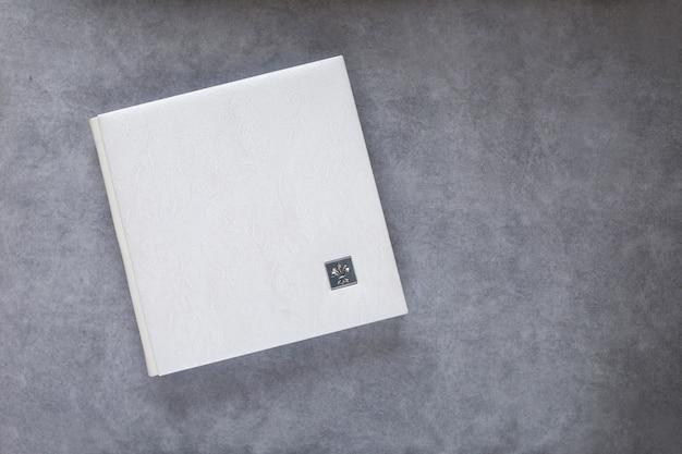 Fotolibro bianco con copertina in pelle. elegante album di foto di matrimonio o di famiglia. bellissimo blocco note o album fotografico con elegante goffratura traforata su sfondo grigio. copia spazio