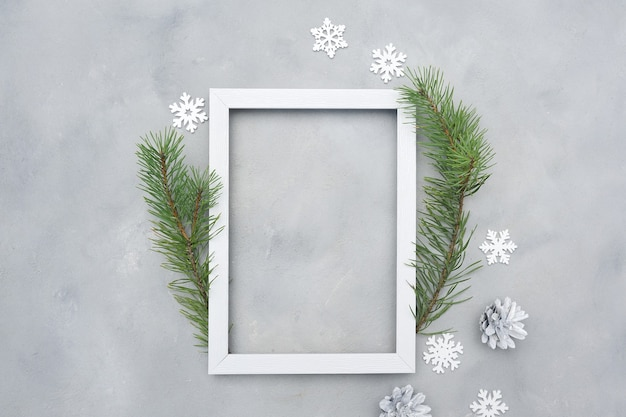 Cornice di natale foto bianca con posto per il testo. vacanza mock up. fiocchi di neve e coni su sfondo grigio.