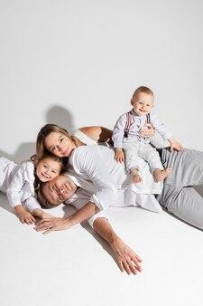 Bianco di studio fotografico con coppia allegra e i loro figli che si rilassano sul pavimento e sorridono.
