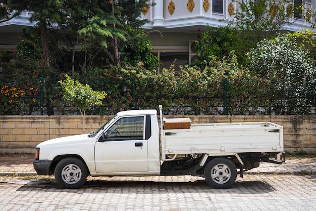 Il pick-up bianco è parcheggiato per strada in una calda giornata estiva sullo sfondo di un parcheggio