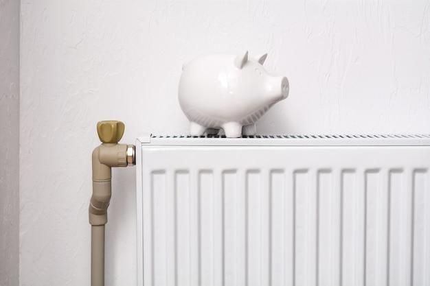 Porcellino salvadanaio bianco sul radiatore. costoso concetto di costi di riscaldamento.